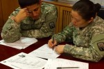 Sgt. Xiaoyan Jiang, right, and Pvt. Luis Jimenez, left, of Alpha Detachment, 106th Financial Management Support Unit, conduct a military pay inquiry analysis during a support mission, Jan. 28, 2016.