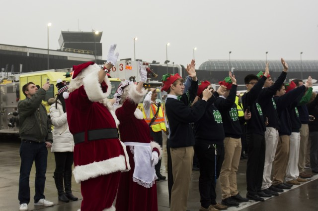 Santa and Mrs. Claus along with volunteer students from Notre Dame College Prep wave to the plane while standing on the tarmac as the Snowball Express taxis out to the runway on Dec. 12. The program is sponsored by American Airlines, coordinating flights from 84 cities via nearly 60 chartered and commercial flights. The Snowball Express is a nonprofit organization established in 2006, providing an all-expenses-paid trip to families across the United States with a mission of bringing hope and new memories to the children of military heroes who have died while on active duty since Sep. 11, 2001. This year marks the 10th annual celebration, 13 Gold Star families from Northern Illinois were on this flight to Dallas for a weekend getaway of festivities and a memorial service for those family members that have been lost. (U.S. Army photo by Staff Sgt. Carrie A Castillo)
