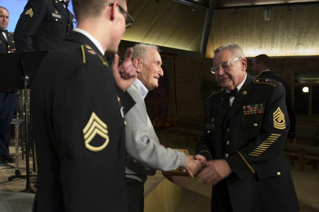 John Pardis, a World War II veteran, is presented with an honorary promotion to sergeant during the 85th Army Band Veterans Day concert.