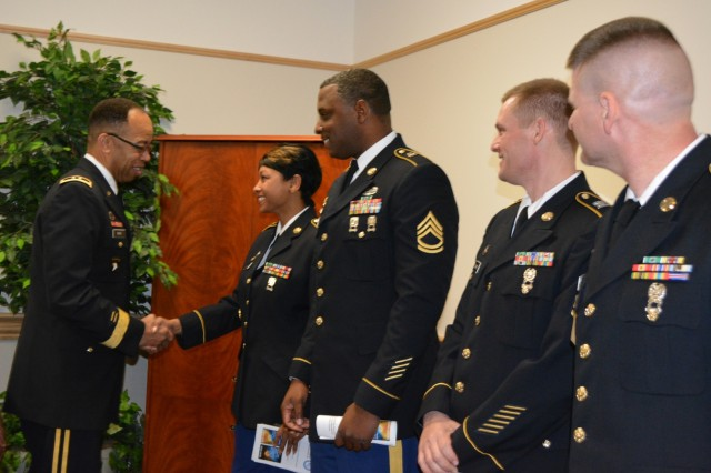 Maj. Gen. A.C. Roper, commander 80th Training Command, presents Sgt. 1st Class Katre Nicholson, Equal Opportunity Advisor, 4th Brigade, 94th Training Division, with his commander's coin while congratulating her for graduating the Equal Opportunity Advisors Reserve Component Course. Roper presented the coin to Nicholson and three other Army Reserve Soldiers from across the 80th TC after delivering the keynote address during the graduation ceremony at the Defense Equal Opportunity Management Institute Patrick Air Force Base, Fla., Feb. 5, 2016. The other three Soldiers from L-R Sgt 1st Class Richard Cobbs, 2nd Brigade 100th Training Division, Sgt 1st Class Norman Wade, 1st Brigade 102nd Training Division, and Master Sgt. Jerry Burton, Headquarters, Headquarters Company 100th Training Division.
