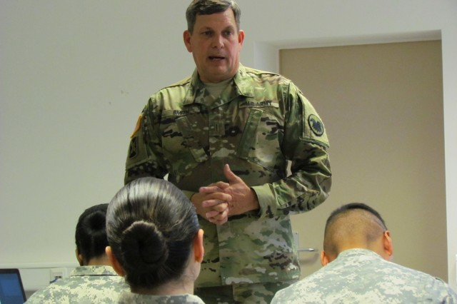 Chief Warrant Officer 5 Russell Smith, Army Reserve Command chief warrant officer, speaks during a town hall meeting with Soldiers in Kaiserslautern, Germany, Feb. 7, 2016.