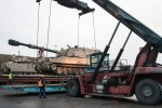 Workers load an M109A6 Paladin onto a trailer at the Port of Klaipeda on Dec. 4, 2015, in Klaipeda, Lithuania. The 624th Movement Control Team, 39th Transportation Battalion (Movement Control), 16th Sustainment Brigade, ensured the Paladin and other pieces of European Activity Set equipment were loaded into vessels bound for Coleman Barracks in Mannheim, Germany, where they will be serviced and stored for use by the next rotational force.