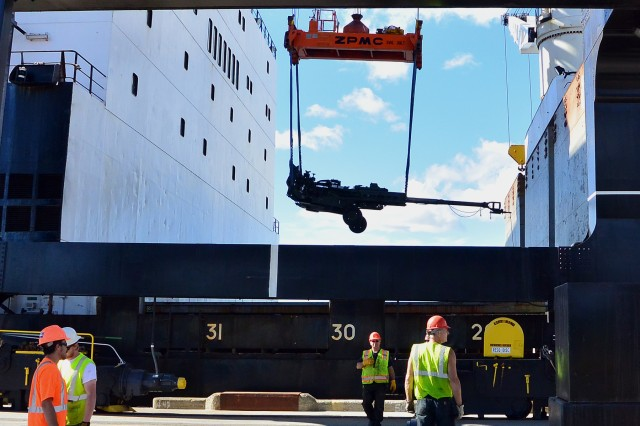 Dock workers at the Port of Anchorage load military vehicles and equipment.