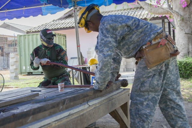 Indonesian Air Force Chief Private Imam Sugiri, with the Engineering Brigade, Indonesian Air Force, cutes rebar as U.S. Army Pvt. 2nd Class James Garcia, with 797th Engineer Company, Vertical, U.S. Army Reserve Center Barrigada, Guam, holds the rebar during the Ban Phromnimit construction project at Sakeao, Thailand, Feb. 2, 2016.