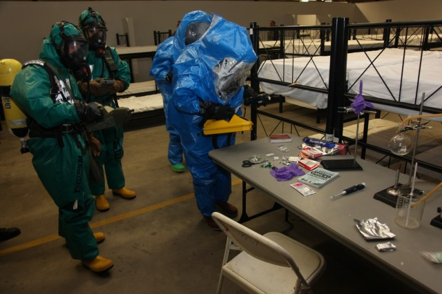 Members, of the 773rd Civil Support Team and the Spanish Unidad Militar de Emergencias, examine a table simulating production of methamphetamine during Exercise Ocean Response, Feb. 11, 2016, at Rhine Ordnance Barracks in Germany.