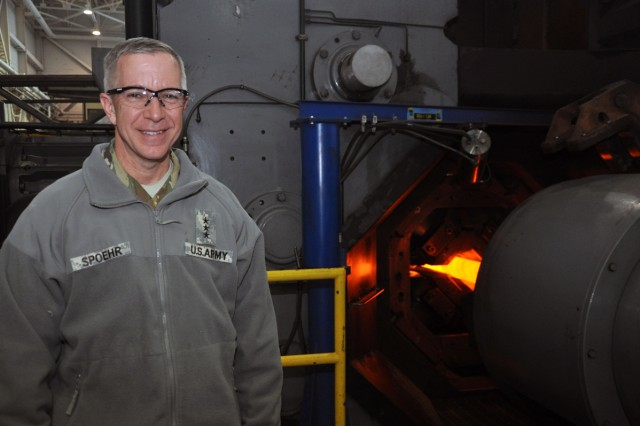 Lt. Gen. Thomas W. Spoehr standing next to the Watervliet Arsenal's rotary forge.