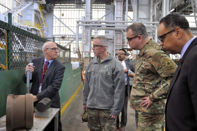 Benet Laboratories Director Lee Bennett, left, explaining a machining operation to Lt. Gen. Thomas W. Spoehr, second from left. While Brig. Gen. David P. Komar and Dr. Charles T. Brandon listen in.