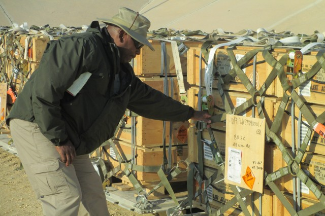 Calvin B. Smith, explosives specialist and munitions packing specialist checks the strapping and identification on a pallet of munitions at Camp Arifjan, Kuwait. Smith is one of six specialists who volunteered to deploy to support the movement of foreign and donated munitions.