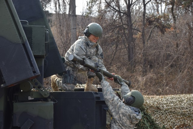 Pfc. Eli Schaap, an air defense battle management system operator assigned to E Battery, 6th Battalion, 52nd Air Defense Artillery Regiment, hands off a M134 Stinger Missile to Pvt. Imaris Suarez during a readiness drill at Osan Air Base, Feb. 16, 2016.  The Soldiers are stationed at Camp Casey, South Korea, and are conducting a cross-training exercise with Patriot air defense forces across the peninsula.