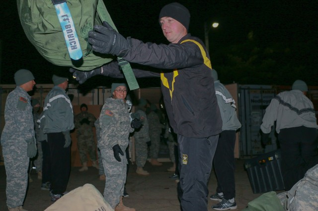 Soldiers from Headquarters and Headquarters Company, 1st Armored Brigade Combat Team, 1st Cavalry Division, unload their shipping containers in the chilly, early morning hours at Camp Hovey, South Korea, Feb. 4. Soldiers in the brigade shipped 56 containers of gear and equipment to the Republic of Korea for use during their nine-month rotation.