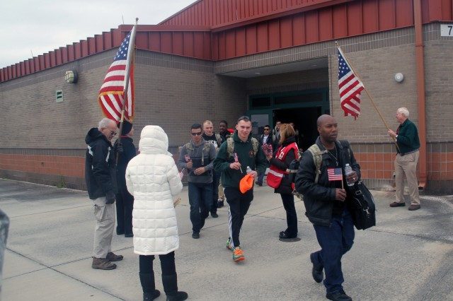 Soldiers of 3rd Battalion, 15th Infantry Regiment, 2nd Infantry Brigade Combat Team, 3rd Infantry Division, pass USO members who bid them farewell Feb. 14, 2016 at Hunter Army Airfield, Ga. Soldiers were given American flags as they left the terminal to embark on their mission to Yavoriv, Ukraine. (U.S. Army photo by Spc. Corey Foreman / Released)
