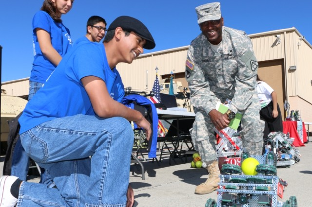 Clint High School students demonstrate to Col. Terrece Harris, director, Capability Package, the robot that they have been working on in their STEM class. The students visited the Integration Motor Pool at Fort Bliss, Texas in support of the Five Star STEM Cup Competition.