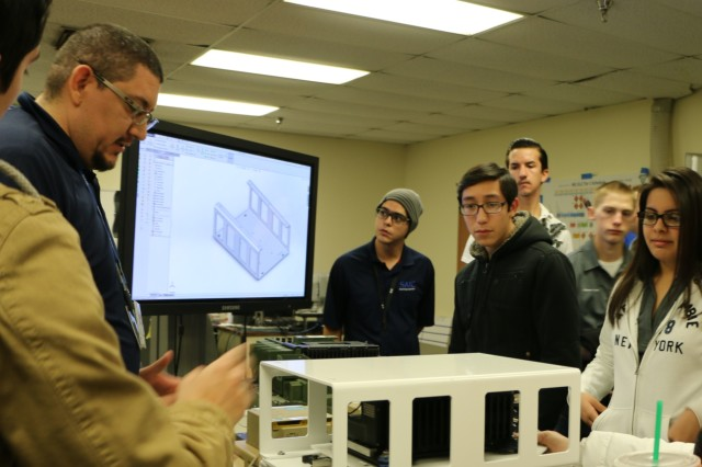Engineers from Capability Package Directorate explain to students from Chapin High School how they draft up an idea and create the final product. This was during the students' field trip to the Integration Motor Pool at Fort Bliss, Texas.