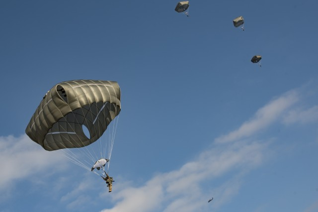 Paratroopers from 4th Battalion, 319th Field Artillery Regiment (Airborne), 173rd Airborne Brigade, seen from the ground, after performing a successful exit from a UH-60L Black Hawk helicopter. Paratroopers conducted over 200 airborne proficiency jumps from two UH-60L Black Hawk helicopters from 3rd Battalion 227th Aviation Regiment, Task Force Spearhead, Feb. 18, 2016, at Bunker drop-zone Grafenwoehr, Germany.