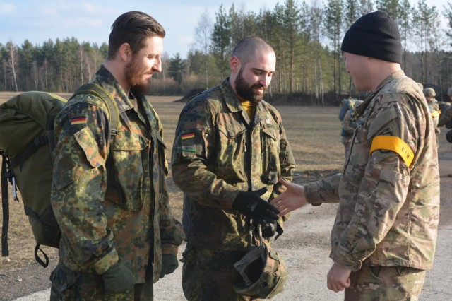 First Lt. Jeffrey Kim from 4th Battalion, 319th Field Artillery Regiment (Airborne), 173rd Airborne Brigade, awards two Bundeswehr Soldiers, from 2nd Panzergrenadierbatallion 122, their Army Parachutist badge after a successful jump from a UH-60L Black Hawk helicopter from 3rd Battalion 227th Aviation Regiment, Task Force Spearhead, Feb. 18, 2016, at Bunker drop-zone Grafenwoehr, Germany.