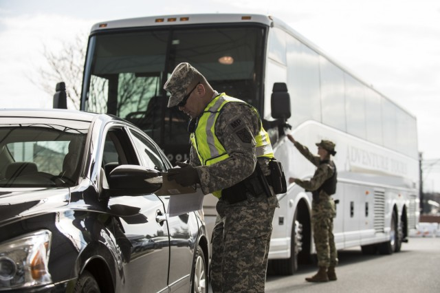 Sgt. Michael Villena (right), U.S. Army Reserve military police Soldier from Manassas Park, Va., with the 352nd MP Company, of the 200th MP Command, checks a driver's paperwork at one of the entry gates to Joint Base Myer-Henderson Hall, as part of a partnership training program with active duty Soldiers from the 289th MP Co., belonging to the 3rd U.S. Infantry Regiment (The Old Guard), to provide law and order, security and patrol support at various active duty installations in the Military District of Washington, Feb. 17. This partnership pilot program began in early February, placing Army Reserve Soldiers on active duty orders for three weeks while working at Joint Base Myer-Henderson Hall, Fort Lesley J. McNair and the Arlington National Cemetery. Soldiers will also support the Military District of Washington with additional duty days throughout the year. (U.S. Army photo by Master Sgt. Michel Sauret)