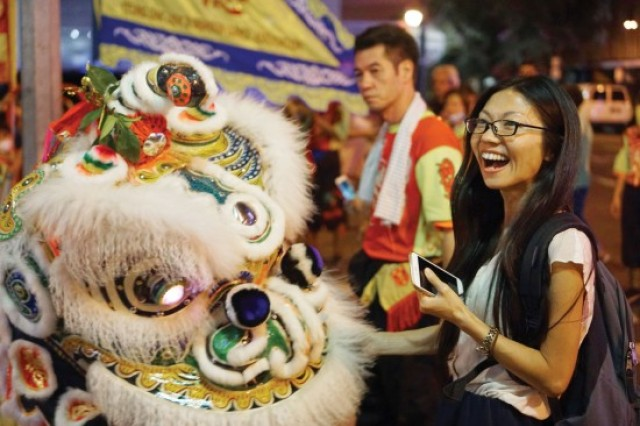Lion dancers from the Yeung Dak Lion and Dragon Dance Association accept a traditional red money packet, or lai see, from one of hundreds in the crowd. The association also played traditional music and lit firecrackers during the celebration.
