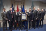 Officials from the Departments of the Army and Navy join JLTV teammates at a Pentagon ceremony held February 19, 2016.  At center, Hon. Frank Kendall, Defense Acquisition Executive, and Col. Shane Fullmer, Joint Project Manager for JLTV, hold the citation.