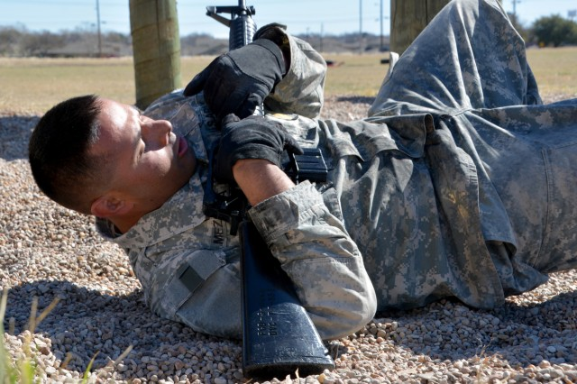 FORT HOOD, Texas -- Staff Sgt. Albert Mezquita, an Observer Controller/Trainer with the 120th Infantry Brigade, Division West, low slides on his back through an obstacle course here Feb. 3. Mezquita, along with three other Soldiers, participated in a 3-day competition for the title of best OC/T. The challenge consisted of a physical fitness assessment, 12-mile road march, obstacle course, and a hand-to-hand combat match. Soldiers received scores for each event and the highest combined score determined the winner.