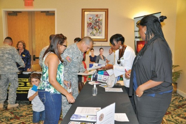 SCHOFIELDBARRACKS, Hawaii -- Ayanna Whitsides (second from right), a Financial Readiness Program volunteer, and Roshetta Carson, an Army Emergency Relief Program specialist (right), provide Spc. Jose Cruz Gomez and his wife, Luz Garcia, with financial resource materials as their son, Josiel Cruz, looks on at a recent Community Readiness Expo.