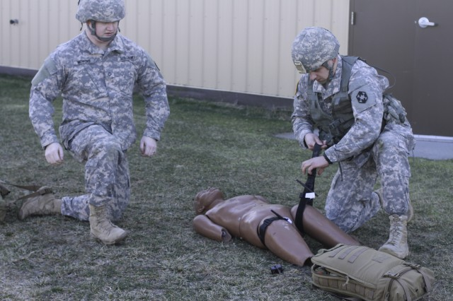 Army Reservists, Private Aric Mowers (Left) and Spc. Ryan Johanson, both health care specialists assigned to the 804th Medical Brigade, Fort Devens, Massachusetts, apply tourniquets to a simulated casualty Feb. 5, while completing the final phase of their annual National Registry EMT basic recertification at Fort Drum's Bridgewater-Vaccaro Medical Simulation Training Center (MSTC).