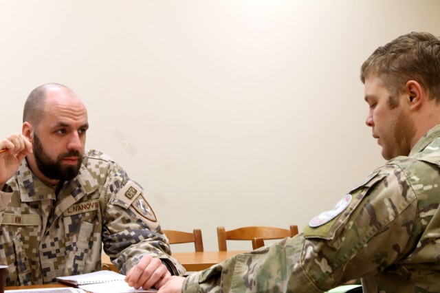 Sgt. Linards Ivanovs, a Latvian Land Force Brigade TACP, and Staff Sgt. James Ingram, a TACP with 2nd Air Support Operations Squadron, discuss aspects of the military decision making process before a simulation on Feb. 18, 2016 at Adazi Military Base, Latvia. The Latvian and U.S. Air Force TACP's have been working together as part of Operation Atlantic Resolve. (U.S. Army photo by Capt. Jennifer Cruz/ Released.)