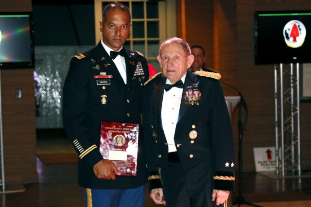Retired Maj. Gen. John K. Singlaub, former Office of Strategic Services officer and founding member of the Central Intelligence Agency (CIA), presents the inaugural award named after himself to Chief Warrant Officer 2 George A. Valdez, a Team Sergeant with 7th Special Forces Group (Airborne), during a special ceremony held at the 2016 USASOC Red and Black Ball, Feb. 20, 2016. The ceremony was held to recognize a Special Forces operator for outstanding achievements and to honor Singlaub. (U.S. Army photo by Sgt. Kyle Fisch/Released)