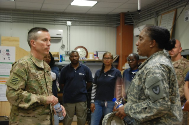 Gloria D. Blake, Theater Provided Equipment-Afghanistan Program Manager, briefs Col. Christopher L. Day, 401st Army Field Support Brigade commander, on the processes her team uses to recover equipment and re-establish an auditability trail to return property to Army property books and maintain accountability for it.