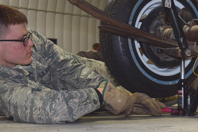 Air Force Airman Cole Calkins practices the removal of a vehicle tire as part of the remove and replace wheel assembly portion of the course.