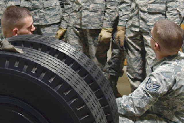 Instructors, Air Force Staff Sgts. Mark Miller and Anthony Dillier respond to questions as students learn removal and replacement of wheel assemblies.