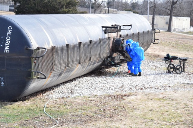 Students in the CBRN Responder Course plug a pressure leak in a simulated railcar crash as part of their final training exercise.