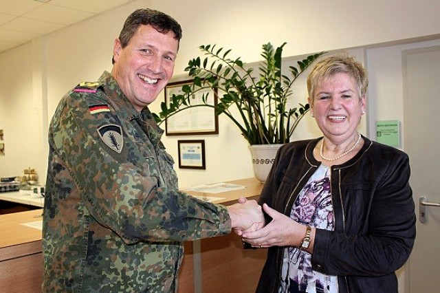 """German Brig. Gen. Markus Laubenthal, U.S. Army Europe chief of staff, presents the """"Coin of Excellence"""" to Heidrun Bodeit, lab director, Jan. 22, for her work in providing AOAP support to Europe, Africa and Southwest Asia. (Photo taken by Steven Stanfill, 405th AFSB Public Affairs)"""