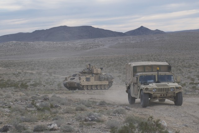 """An M2A3 Bradley Fighting Vehicle from 1st Battalion, 12th Cavalry Regiment, 3rd Armored Brigade Combat Team, 1st Cavalry Division provides rear security within a convoy in the """"box"""" at the National Training Center in Fort Irwin, Calif. The Soldiers of 1-12 Cav. are giving support and receiving support from their enabler units, also from the 1st Cav. Div. - the 3rd Engineer Battalion and the 2nd Battalion, 82nd Field Artillery Regiment. (U.S. Army photo by 1st Lt. Roque Mesa, 1st Battalion, 12th Cavalry Regiment, 3rd Armored Brigade Combat Team UPAR (released))"""