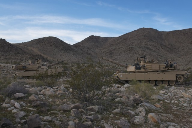 """Two M1A2 Abrams tanks from 1st Battalion, 12th Cavalry Regiment, 3rd Armored Brigade Combat Team, 1st Cavalry Division maneuver to a defensive posture to provide security in the """"box"""" of the National Training Center in Fort Irwin, Calif. Soldiers of 1-12 Cav. are deployed to NTC in support of the 3rd Cavalry Regiment's Decisive Action rotation. (U.S. Army photo by 1st Lt. Roque Mesa, 1st Battalion, 12th Cavalry Regiment, 3rd Armored Brigade Combat Team UPAR (released)"""