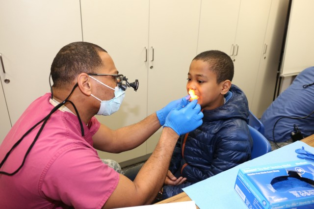 Maj. Demarcio Reed, commander of DENTAC-J and comprehensive dentist, conducts a dental screening with Shawn Litt, fourth-grader, during a visit to Arnn Feb. 24-26 for NCDHM. (U.S. Army Photo by Lance D. Davis)