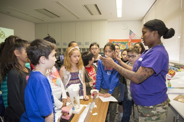 Spc. Qwameshia Plummer, preventive dentistry, assigned to DENTAC-J, talks about the importance of flossing with Arnn fourth-graders and demonstrates how to properly floss during a visit to the school Feb. 24-26 for NCDHM. (U.S. Army photo by Lance D. Davis)