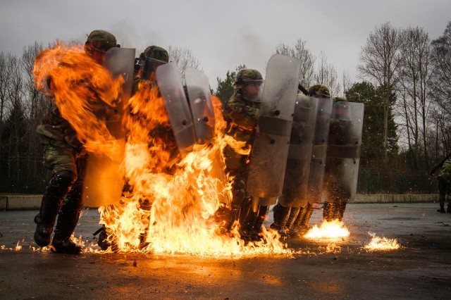A unit of Moldavian soldiers push through a wall of fire, Feb. 17, during fire-phobia training. As part of their pre-KFOR deployment, multinational and United States service members pass through the Joint Multinational Readiness Center where they must complete a rigorous series of training scenarios before moving on to the NATO KFOR operation. The KFOR MRE 21 is based on the current operational environment and is designed to prepare the unit for peace support, stability, and contingency operations in Kosovo in support of civil authorities to maintain a safe and secure environment.