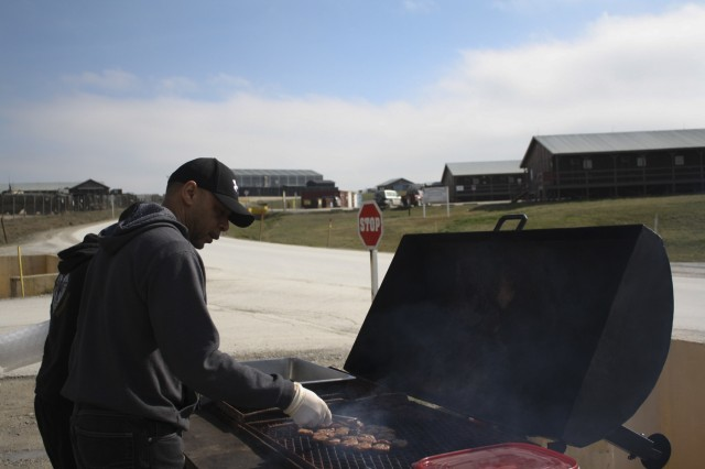 "Eddie Fears, the officer in charge of the Camp Bondsteel, Kosovo, post office for Area Support Team-Balkans, grills hamburgers and hot dogs for Multinational Battle Group-East Soldiers to enjoy during cookout and postal ""rodeo,"" Feb. 27, 2016, at Camp Bondsteel, Kosovo. Fears and the troops provided free food and longer postal hours to encourage Soldiers preparing to return home to mail packages early and avoid the last-minute rush. The post office mails over 200 packages and letters a day and serves not only Camp Bondsteel, but also Soldiers assigned to MNBG-E's Forward Command Post at Camp Marechal de Lattre de Tassigny. (U.S. Army photo by Sgt. Gina Russell, Multinational Battle Group-East)"