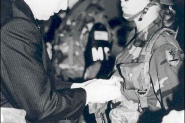 Pvt. 1st Class Charla Shull receives her Missouri National Guard Panama Service Ribbon from Gov. John Ashcroft when she and the other members of the 1138th Military Police Company returned home from Operation JUST CAUSE.