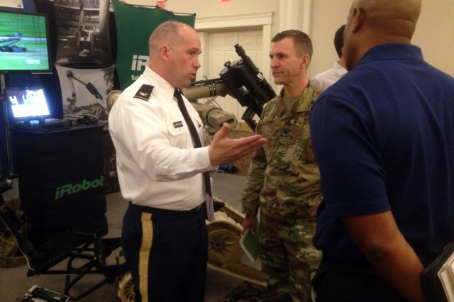 Col. Kurt T. Thompson, director of the Soldier Division, TRADOC Capabilities Manager-Soldier, left, speaks with Col. William Chlebowski, Army Capabilities Integration Center, March 2, 2016, during a conference in Springfield, Va.