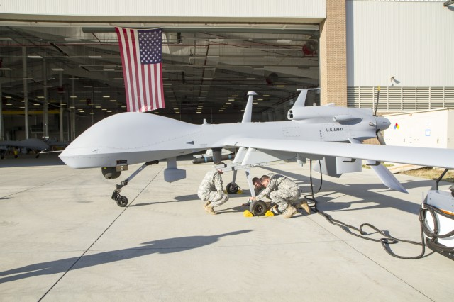 Soldiers from Company E, 3rd Combat Aviation Brigade, perform pre-flight checks on the MQ-1C Gray Eagle unmanned aerial system before the Mass Fire Mission on Fort Stewart, Ga., March 1. For the first time ever, Division Artillery teamed with the MQ-1C Gray Eagle unmanned aerial system, which was utilized for a wide range of purposes including target identification, observing the rounds as they are fired, and assessing battle damage.