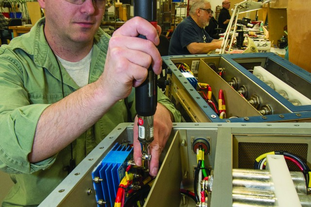 Bill Laury, an electronics worker at Tobyhanna Army Depot, finishes installing a battery combiner in a Power Distribution Unit. Battery combiners allow two or more battery banks to be automatically combined (connected) during charging, allowing a single charge source to charge multiple battery banks.