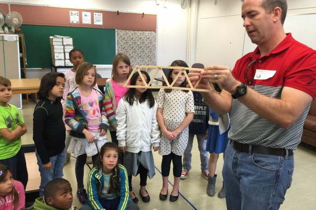 Joe Godwin, civil engineer with the Japan District's Okinawa Area Office, demonstrates the construction of a bridge out of Popsicle sticks and toothpicks to students of Kadena Elementary School in Okinawa.
