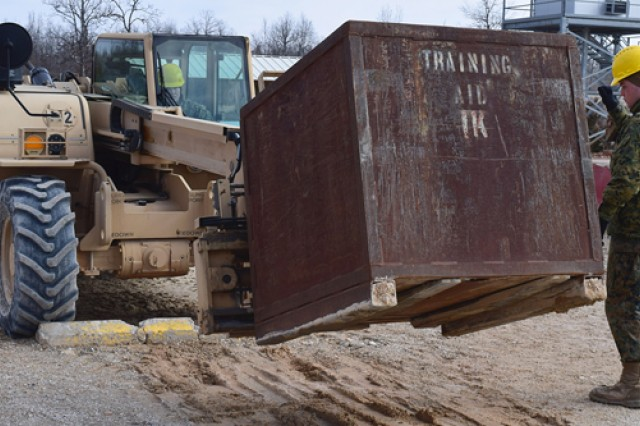 A Marine operates a Light Capacity Rough Terrain Forklift, under the direction of a ground guide.