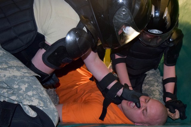 Sgt. 1st Class Joshua Garner, Advanced Individual Training platoon sergeant, playing the role of an uncooperative detainee, is forced to comply by use of a pressure point taught during unarmed self-defense during a forced-cell move training exercise as part of corrections and detention specialist training at Fort Leonard Wood.