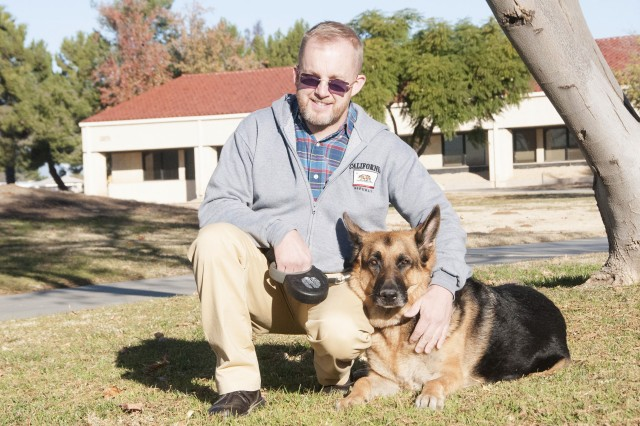 David Cunningham, director of Psychological Health (DPH) for the 163rd Attack Wing, takes a moment for a photo with the wing's therapy dog, Jax. Jax is a German shepherd who is completing training as a certified therapy dog for the 163rd Attack Wing at March Air Reserve Base.