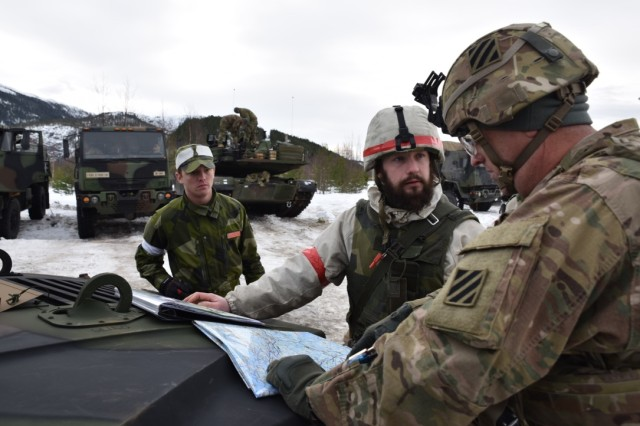 Swedish Lt. Jakob Horck (center), 212th Engineer Company, Gota Engineer Regiment, Swedish Army, and 1st Sgt. Victor Haven, 2nd Battalion, 7th Infantry Regiment, 1st Armored Brigade Combat Team, 3rd Inf. Division, discuss locations on a map during Exercise Cold Response 16.