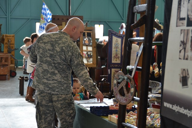 ANSBACH, Germany (March 4, 2016) -- Sgt. Luke Park carries his daughter Laurel while he and daughter Lydia look at prices at the bazaar. The Ansbach Spouses' and Civilians' Club and U.S. Army Garrison Ansbach's Family and Morale, Welfare and Recreation held the grand opening for the Near and Far Spring Bazaar today at Hangar 2, Katterbach Kaserne. (U.S. Army photo by Bryan Gatchell, USAG Ansbach Public Affairs)