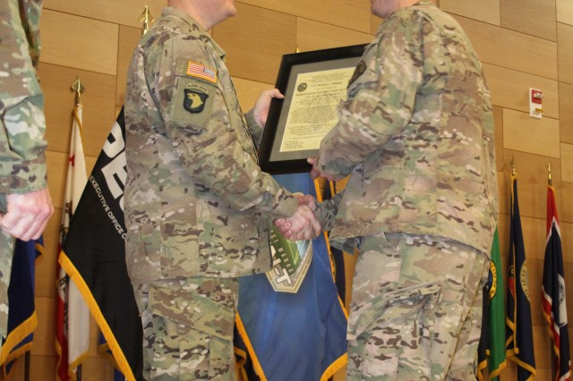 Lt. Col. Michael Williams, incoming product manager for Warfighter Information Network-Tactical (WIN-T) Increment 2, (right) accepts the program's charter from Col. Gregory Coile, project manager for WIN-T, (left) at the Myer Auditorium at Aberdeen Proving Ground, Md., on March 4, 2016. (U.S. Army photo by Lynn Harkins, PM WIN-T graphics)