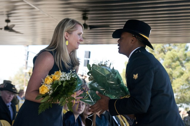 Spc. Teliferro Mitchell, driver for the 3rd Armored Brigade Combat Team's, 1st Cavalry Division command sergeant major, hands Allison Woodward, spouse of Col. John Woodward, the incoming brigade commander, a bouquet of yellow roses. (U.S. Army photo by Sgt. Brandon Banzhaf, 3rd Armored Brigade Combat Team PAO, 1st Cavalry Division)